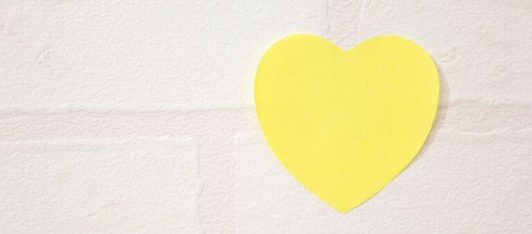Heart-shaped post-it on brick wall